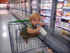 crianca em carrinho de supermercado