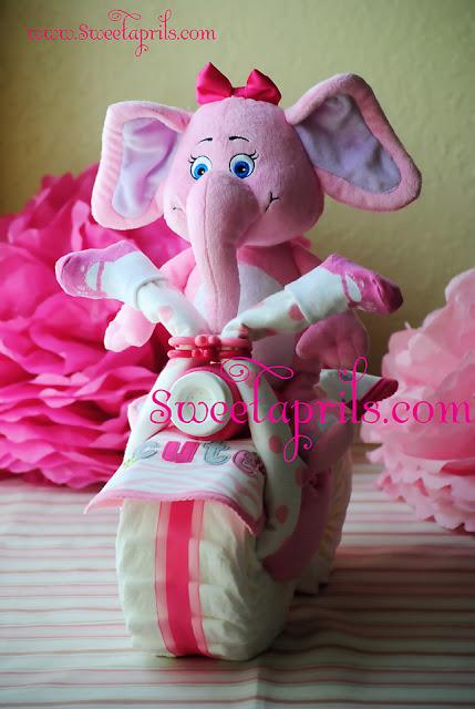 bolo de fraldas de moto com elefante rosa de pelucia